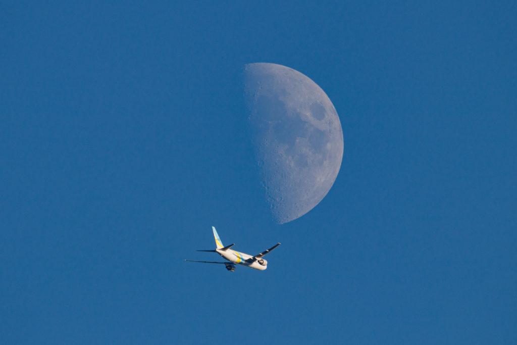 月の下を通る飛行機